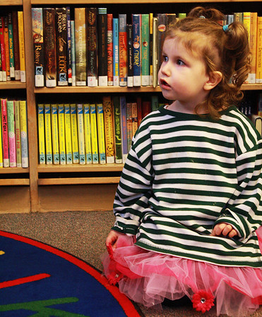 Emerald Jakes, 2, of Manchester, listens as Sara Collins, Manchester Public Library's children's librarian, reads from a book on Wednesday morning during the Mother Goose Story Time. Jesse Poole/Gloucester Daily Times Dec. 07, 2011