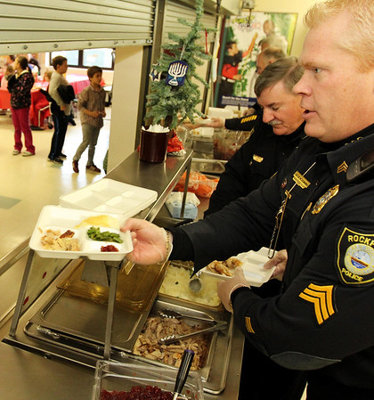 Courtesy photo/Gloucester Daily Times. Rockport: Members of the Rockport Police Department served lunch to Rockport Elementary School students on Friday. From front to back are Sgt. Mark Schmink and Chief John McCarthy serving a turkey dinner to students. The school and police department have been planning to do this for a while and hope to make it a new tradition.