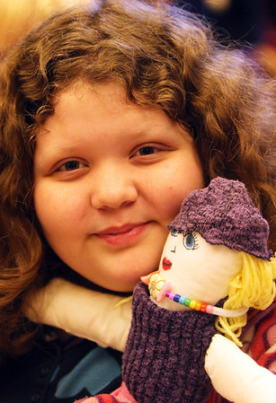 ALLEGRA BOVERMAN/Staff photo. Gloucester Daily Times. Manchester: Sasa Willems, 10, shows off the doll she made during the Manchester Public Library's annual Gift Making and Wrapping workshop held on Thursday afternoon. There were more than 30 children busy making a variety of gifts - from calendars to beaded jewelry and picture frames and more. Then they could wrap them.
