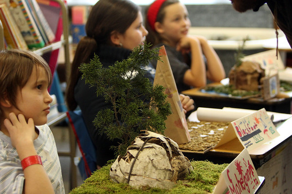 ALLEGRA BOVERMAN/Staff photo. Gloucester Daily Times. Gloucester: West Parish third graders, front, to back, Natasha Baumgaertel, Janaya Cluney, and Willa Brosnihan discuss their research about  various Native American nations during their class's Native American presentation on Wednesday at the school. Each student in the class did extensive research about different Native American nations, wrote up their research, complete with illustrations, and created dioramas of how each nation set up their homes and then presented their findings to other students and parents.