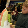 ALLEGRA BOVERMAN/Staff photo. Gloucester Daily Times. Gloucester: Hunter Gillis, 8, paints a buoy at Art Haven on Friday afternoon. Organizers said there were about 66 children in the first hour working on decorated buoys to be hung on the Lobster Trap tree on Satuday before it will be lit.