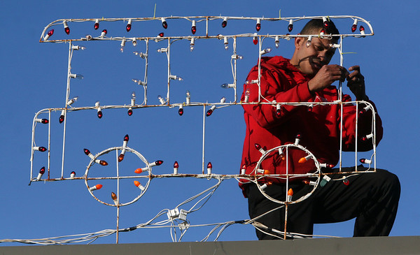 ALLEGRA BOVERMAN/Staff photo. Gloucester Daily Times. Gloucester: Joe Costa, of Precision Roofing Services, changes light bulbs on a holiday display on the roof of the Whittemore Street business on Friday afternoon.