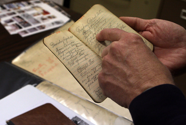 ALLEGRA BOVERMAN/Staff photo. Gloucester Daily Times. Gloucester: Erik Ronnberg, Jr., shows the logbooks of his father, Erik Ronnberg, Sr., when he worked on the Bright Star.