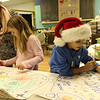 "ALLEGRA BOVERMAN/Staff photo. Gloucester Daily Times. Gloucester: During a ""Christmas Collaboration"" workshop at Art Haven on Friday afternoon, participants would draw, write, or stamp distinctive pictures or phrases on one another's posters and make a collaborative piece of art to hang up during the holidays. From left are: Aja Heussi of Art Haven, Lily Marshall, 8 and Tyler Rodolosi, 8."