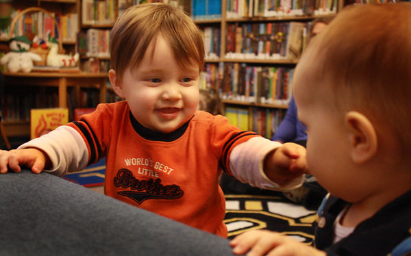 Freddy Jakes, 2, pokes at his friend Devin Peavey, nearly 2, at the Manchester Public Library on Wednesday morning. Jesse Poole/Gloucester Daily Times Dec. 07, 2011