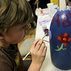 ALLEGRA BOVERMAN/Staff photo. Gloucester Daily Times. Gloucester: Abby Webb, 9, carefully paints a buoy at Art Haven on Friday afternoon. Organizers said there were about 66 children in the first hour working on decorated buoys to be hung on the Lobster Trap tree on Satuday before it will be lit.