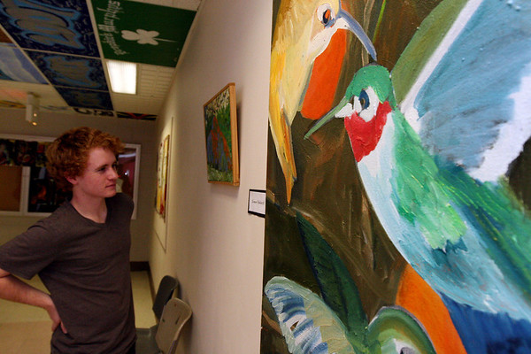 ALLEGRA BOVERMAN/Staff photo. Gloucester Daily Times. Rockport: During the opening of Gallery 24 @ Jerdens Lane Rockport High School junior William Gleckner examines the paintings of Simon Paddock, an art teacher at the elementary school.