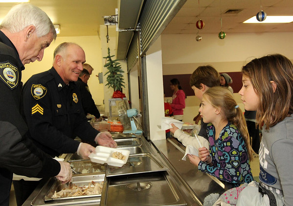 Courtesy photo/Gloucester Daily Times. Rockport: Members of the Rockport Police Department served lunch to Rockport Elementary School students on Friday. The school and police department have been planning to do this for a while and hope to make it a new tradition. From left, Patrolman Roger Lesch and Sgt. Bob Tibert and in the background, Chief John McCarthy and Sgt. Mark Schmink, serve turkey dinners to the students. Getting their food and talking with them are, at far right, fifth grader Olivia Kendall-Scalfani and fourth grader Carling Berglund.