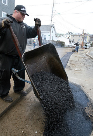 ALLEGRA BOVERMAN/Staff photographer. Gloucester Daily Times. Gloucester: At front, Bruce MacArthur of McGinnis Paving of Beverly Farms works with Kevin Levesque, background, to repave Webster Street where gas lines were just worked on Tuesday afternoon.