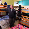Jim Noble, Action's shelter manager, stands in a crowded bedroom at the Action's Rogers Street location. Jesse Poole/Gloucester Daily Times Dec. 05, 2011