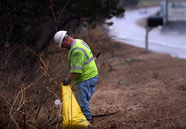 ALLEGRA BOVERMAN/Staff photo. Gloucester Daily Times. Essex: Mike Bourque, a massDOT employee, clears debris from the shoulder of Route 133 in Essex on Wednesday afternoon. He said he can easily fill six or seven trash bags just picking up trash from a small area of the roadside. This is one of many road-related jobs he regularly does in his particular territory of Essex, Ipswich, Hamilton, Wenham and Beverly.