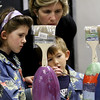 ALLEGRA BOVERMAN/Staff photo. Gloucester Daily Times. Gloucester: Members of the Mckay family paint buoys at Art Haven on Friday afternoon. Organizers said there were about 66 children in the first hour working on decorated buoys to be hung on the Lobster Trap tree on Satuday before it will be lit. From left are Caroline, 7, brother Liam, 5, and their mom, above, Erin.