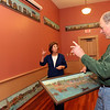 ALLEGRA BOVERMAN/Staff photo. Gloucester Daily Times. Rockport: Karen Berger, left, chair of the Rockport town owned art committee, talks with Buddy Woods, who is on the Community House board and used to be in the Sandy Bay HIstorical Society, about 13 historical artworks that are both being restored and being rehung in the two community rooms of Community House on Wednesday. The town now owns the artworks, which were done by Stephen Urquhart, and had gotten them from the Sandy Bay Historical Society.