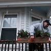 ALLEGRA BOVERMAN/Staff photo. Gloucester Daily Times. Gloucester: Chris Jedrey strings some of his colored lights along his porch on Centennial Avenue on Tuesday afternoon.