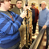 ALLEGRA BOVERMAN/Staff photo. Gloucester Daily Times. Gloucester: Gloucester High School senior Chris Taylor, far left, puts together a new baritone saxophone that was obtained by members of the former Atlantic Brassman Senior Drum & Bugle Corps, including Gaspar LaFata, far right, and Billy Goulart, second from right. Music director Dave Adams is second from left. The organization had money to use and wanted to help the music department.