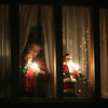 ALLEGRA BOVERMAN/Staff photo. Gloucester Daily Times. Gloucester: Lighted Santa and Mrs. Claus statues are carefully arranged in a window along Washington Street on Monday evening.