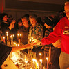 ALLEGRA BOVERMAN/Staff photo. Gloucester Daily Times. Gloucester: Dozens of menorahs were lit for the first night of Hanukkah during the community Hanukkah party held at Temple Ahavat Achim in Gloucester on Tuesday evening. At right is Amalia Cymrot-Wu, 12, left, and Jerry Rosenberg, right, light a menorah together.