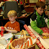 ALLEGRA BOVERMAN/Staff photo. Gloucester Daily Times. Manchester: From left, Declan Kirk, 7, and Connor Cunningham, 8, wrap gifts they made during the Manchester Public Library's annual Gift Making and Wrapping workshop held on Thursday afternoon. There were more than 30 children busy making a variety of gifts - from dressed-up dolls and calendars to beaded jewelry and picture frames and more. Then they could wrap them.