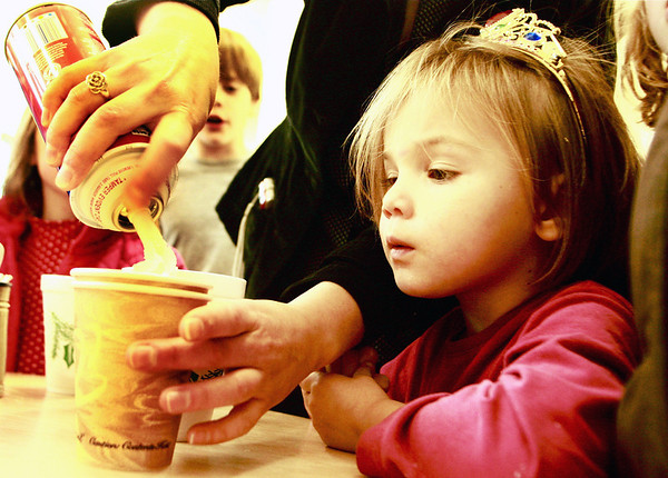 Essex-Zealand Gould, 3, of Essex, wears a tiara and intensely watches as children's librarian April Wanner tops her cup of hot cocoa off with whipped cream (upon request) on Tuesday afternoon at the T.O.H.P. Burnham Library, all in celebration of National Hot Cocoa Day. Jesse Poole/Gloucester Daily Times Dec. 13, 2011