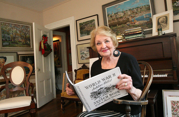 ALLEGRA BOVERMAN/Staff photo. Gloucester Daily Times. Rockport: Carol Carlson in the Carlson Gallery at her home in Rockport. Her late husband, Sven Ohrvel Carlson, were and are both artists and musicians. She is holding a published sketch book he did during his service in World War II.