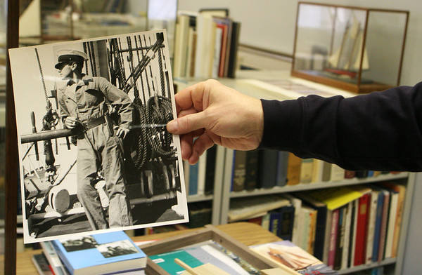 ALLEGRA BOVERMAN/Staff photo. Gloucester Daily Times. Gloucester: Erik Ronnberg, Jr., shows a picture of his father, Erik Ronnberg, Sr. from the early 1940s.
