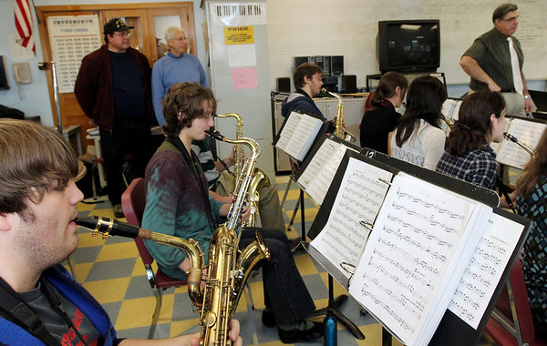 ALLEGRA BOVERMAN/Staff photo. Gloucester Daily Times. Gloucester: Gloucester High School senior Chris Taylor, bottom, plays a baritone saxophone during rehearsal of the jazz band Docksiders on Tuesday. A <br /> new baritone saxophone was just obtained by members of the former Atlantic Brassman Senior Drum & Bugle Corps, including Billy Goulart, left, and Gaspar LaFata, standing, background. Music director Dave Adams is at far right. The organization had money to use and wanted to help the music department.