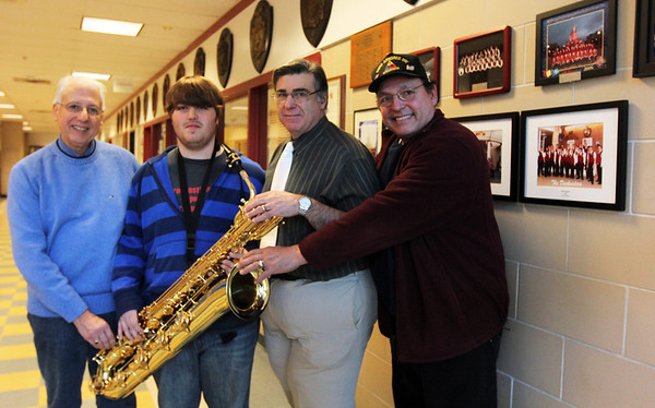 ALLEGRA BOVERMAN/Staff photo. Gloucester Daily Times. Gloucester: Gloucester High School senior Chris Taylor, second from left, with a new baritone saxophone that was obtained by members of the former Atlantic Brassman Senior Drum & Bugle Corps, including Gaspar LaFata, far left, and Billy Goulart, far right. Music director Dave Adams is second from right. The organization had money to use and wanted to help the music department.