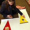 ALLEGRA BOVERMAN/Staff photo. Gloucester Daily Times. Manchester: Whitney Johnson, 9, wraps pennants she designed during the Manchester Public Library's annual Gift Making and Wrapping workshop held on Thursday afternoon. There were more than 30 children busy making a variety of gifts - from dressed-up dolls and calendars to beaded jewelry and picture frames and more. Then they could wrap them.