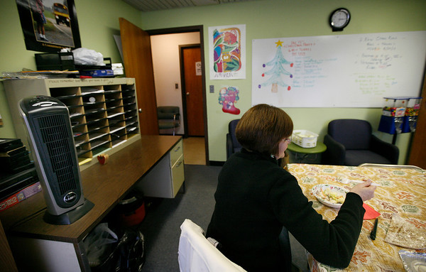 Allegra Boverman/Gloucester Daily Times. An oscillating space heater, on the table at far left, is one of two space heaters in the driver's break room in the Gloucester Public Schools Transportation Department in the Fuller School building. A bus driver eats her lunch there on Tuesday afternoon.