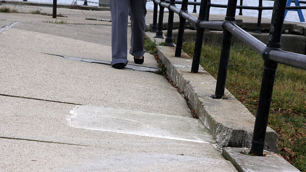 Allegra Boverman/Gloucester Daily Times. Damage along the Stacy Boulevard seawall very close to the Cut Bridge. Damage includes separation and cracking in the pavement and wall itself and broken railings. The pavement is buckled and tilting in towards the Cut here.