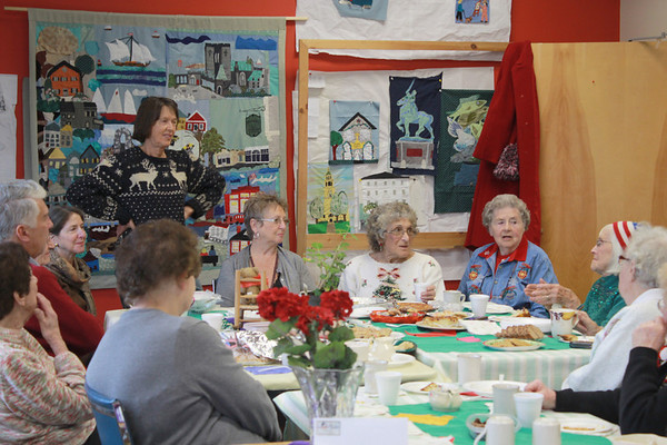 Jim Vaiknoras/Gloucester Times: Juni Van Dyke describes some of the quilts at the neighborhood quilting project Christmas party <br />  at the Rose Baker Senior Center Monday. Eight of their quilts are on display at the library, they are working on eight others.