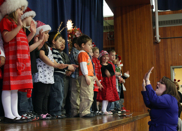 MARIA UMINSKI/GLOUCESTER DAILY TIMES Music teacher Sarah Doran sings along with her students during the Veterans Memorial Elementary Holiday Sing-a-Long on Thursday.