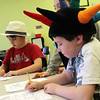 Allegra Boverman/Gloucester Daily Times. It was Crazy Hat Day at the Gloucester Community Arts Charter School on Friday. Griffin Towne, right, and Caleb Kent, left, work on math problems wearing their hats of choice.