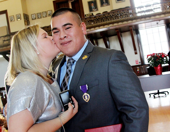 Allegra Boverman/Gloucester Daily Times. Adam Curcuru of Gloucester received a Purple Heart medal on Friday for his injury during his service as a lead gunner in the Third Battalion Sixth Marines in Afghanistan. He is being kissed by his wife Janessa after the ceremony at City Hall.