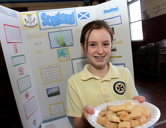 Allegra Boverman/Gloucester Daily Times. St. Ann Middle School sixth grader Maggie Taraska shows off shortbread, a food of Scotland. She was talking about Scotland during the Heritage Fair. Her family is from Scotland and she is descended from the poet Robert Burns. She will be traveling there in July for the first time. She was talking about him, the house he lived in, his poems and other facts about Scotland during the event. A cookbook featuring 40 recipes from around the world was put together by the middle school students and teachers and proceeds help fund their activities for next year.