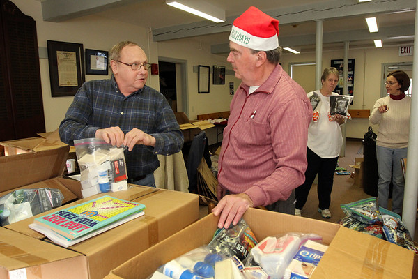 Allegra Boverman/Gloucester Daily Times. From left, Dana Rankin and Ray Fisher of Gloucester were helping to pack up care packages for eight soldiers serving in Afghanistan for the holidays at the Office of Veterans Service on Wednesday morning. They were putting toiletries of all kinds in the boxes, including shampoo, soap, deoderant, wipes, lotion, toothpaste and so on. Also helping are, in back, from left, Susan Canning and Lucia Amero of the Veterans Services office.