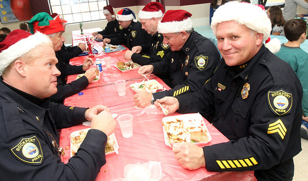 Allegra Boverman/Gloucester Daily Times. The Rockport Police Department served lunch to Rockport Elementary School students on Thursday, the second year they have done so. Leftovers from the lunch, which included turkey, stuffing, mashed potatoes, gravy, cranberry sauce, string beans and rolls, were brought to the Action homeless shelter in Gloucester immediately following.  About a dozen officers were on hand, including Lt. Mark Schmink, lower left, Sgt. Bob Tibert, lower right, Chief John McCarthy, next to him, special officer Roger Lesch, second from left, and others.
