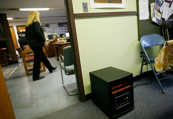 Allegra Boverman/Gloucester Daily Times. A space heater at the right of the door frame, is one of two  in the driver's break room in the Gloucester Public Schools Transportation Department in the Fuller School building. Kathy Verga, the manager of the department, is in the background.