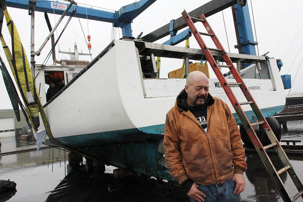 """Allegra Boverman/Gloucester Daily Times. Capt. Dave Marciano's boat, """"Hard Merchandise"""" became submerged in its slip at Gloucester Marine Railways over the weekend. Marine Services of Salisbury lifted it up and out of the water."""