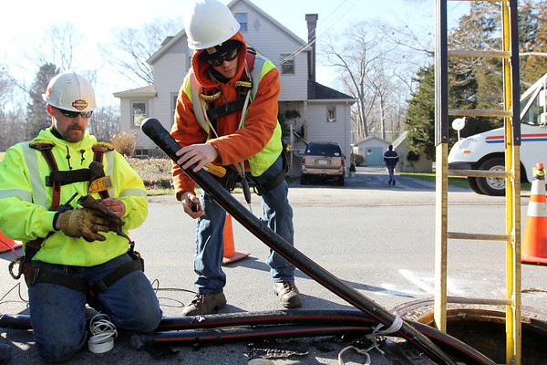 Allegra Boverman/Gloucester Daily Times. From left, ElecComm employees Bob Whitney and Leo Keefe were installing cable along Magnolia Avenue in Gloucester on Thursday morning. They are working with National Grid to put cables underground to improve service reliability from Beverly to Cape Ann.