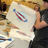 Allegra Boverman/Gloucester Daily Times. Manchester Essex Regional High School freshman Scotty Franklin makes a print of a flounder he and his buddies painted red, white and blue during a two day workshop with visiting artist Joseph Higgins of Salem.