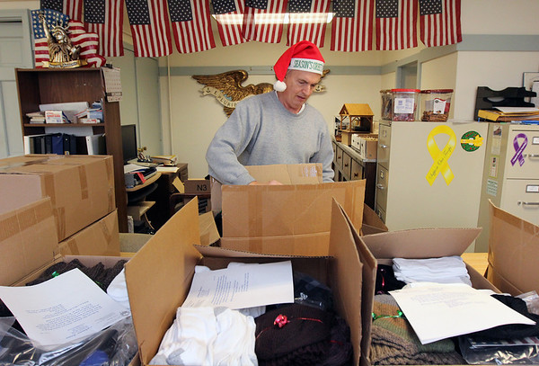 Allegra Boverman/Gloucester Daily Times. Steve Canning of Gloucester seals boxes of warm clothing, blankets, socks, scarves, gaitors, helmet liners and more for eight soldiers serving in Afghanistan from the area at the Office of Veterans Services on Wednesday morning. The blankets were donated by Essex County Sheriff Frank Cousins.