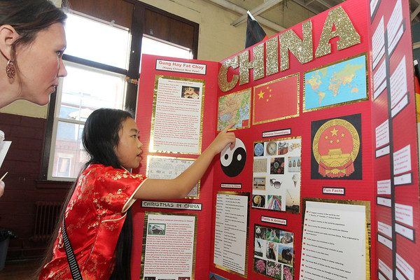 Allegra Boverman/Gloucester Daily Times. St. Ann Middle School sixth grader Maya Acker, right, shows Nicole Poliskey, mother of one of Acker's classmates, where she's from in China during the Heritage Fair on Tuesday. <br /> The middle school students have spent time studying countries where they have ancestors and family or are from themselves, and put on display information about their cultures, customs, made food native to those countries and discussed how Christmas is celebrated in those countries. The students and teachers also created a cookbook with 40 recipes from around the world and proceeds from the cookbook sales will fund middle school activites for next year.