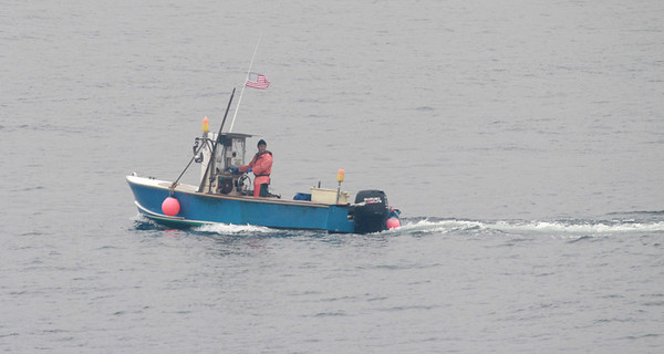 Jim Vaiknoras/Gloucester Times: A lobsterman lays traps off Bearskin Neck in the fog in Rockport Monday afternoon.