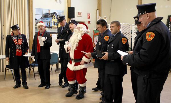 Jim Vaiknoras/Gloucester Times: Gloucester Firefighters sing carols, along with Santa, to residences at the Rose Baker Senior Center Monday.