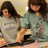 Allegra Boverman/Gloucester Daily Times. Manchester Essex Regional High School seniors Natalie Caponigro, left, and Tiffany Vander Laan team up to make a print of a red drum fish during a two day workshop with visiting artist Joseph Higgins of Salem.