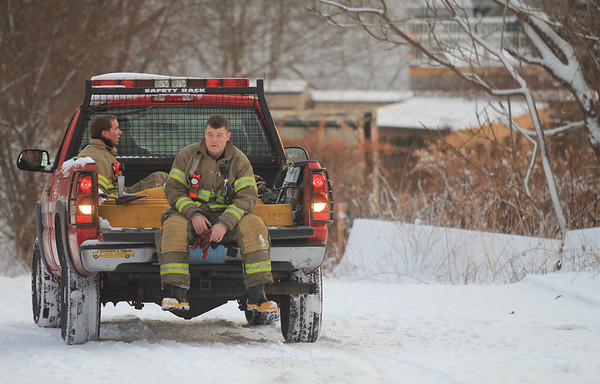 Jim Vaiknoras/Gloucester Times:Two fire fighter rest on the back of a pick up truck after gathering hoses at the scene of a fire at a storage facility on Sargent Street in Gloucester.