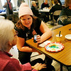 Allegra Boverman/Gloucester Daily Times. The Grace Center, Inc. Inc. held a celebration of its first year on Wednesday. Jennifer Burke, center, shows volunteer Elaine Brown, left, some photos from her phone during the event.