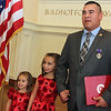 Allegra Boverman/Gloucester Daily Times. Cpl. Adam Curcuru of Gloucester received a Purple Heart medal on Friday for his injury during his service as a lead gunner in the Third Battalion Sixth Marines in Afghanistan. He is with his daughters Kiara, 3, far left, and Kajsa, 7, after the ceremony.