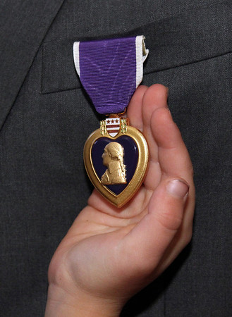 Allegra Boverman/Gloucester Daily Times. Adam Curcuru of Gloucester received a Purple Heart medal on Friday for his injury during his service as a lead gunner in the Third Battalion Sixth Marines in Afghanistan. His daughter Kajsa, 7, holds the medal.